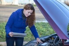 Mulher um motorista com o touchpad que repara o carro quebrado Fotografia de Stock