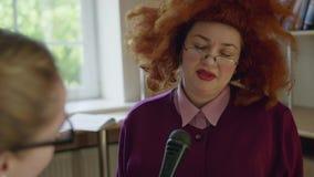 Mulher unenthusiastic engraçada na peruca vermelha que dá a entrevista no microfone vídeos de arquivo