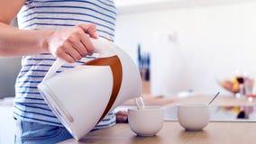 Mulher Unrecognisable que prepara o café ou o chá Água de derramamento em um copo Imagem de Stock