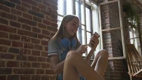 A mulher urbana bonita está lendo a mensagem de texto no telefone celular ao sentar-se no skate perto da parede de tijolo vermelh filme