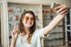 Mulher urbana elegante emotiva na loja do ótico que está sobre suportes com vidros ao tomar o selfie em à moda imagens de stock