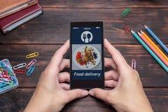 A mulher usa o app no móbil para pedir a entrega do alimento foto de stock royalty free