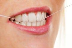A mulher usa o floss dental fotografia de stock