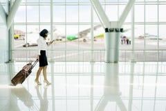 A mulher usa o telefone celular ao andar no aeroporto imagens de stock royalty free