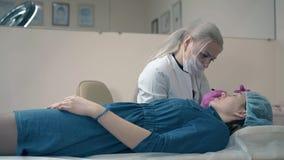 A mulher usa o tweezer para trabalhar com movimento lento das testas do cliente filme