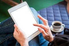 A mulher usa a tabuleta ao relaxar em casa com café no sofá fotos de stock