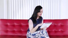 A mulher usa a tabuleta no sofá vermelho em casa video estoque