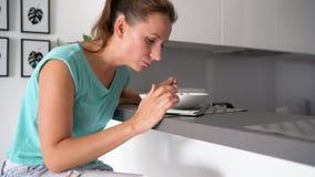 A mulher usa um smartphone ao comer seu café da manhã filme