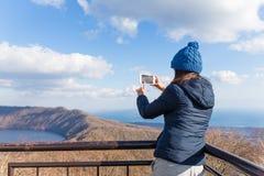 A mulher vai caminhar e tomar a foto no telefone celular imagens de stock