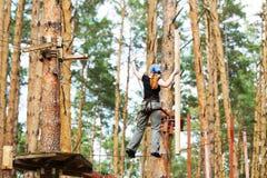 A mulher vai dentro para o alpinismo em árvores altas imagem de stock