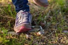 A mulher vai na grama nas sapatilhas Risco de piso em uma lasca de vidro de garrafa quebrado Imagens de Stock