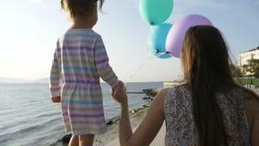 A mulher vai pela mão com uma menina bonita pequena na manhã no beira-mar da cidade video estoque