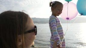 A mulher vai pela mão com uma menina bonita pequena na manhã no beira-mar da cidade vídeos de arquivo