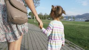 A mulher vai pela mão com uma menina bonita pequena no parque do verão da manhã filme