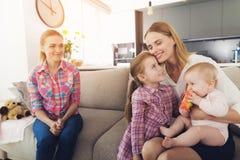 A mulher veio em casa e abraça suas crianças Uma baby-sitter está sentando-se ao lado deles Fotos de Stock Royalty Free