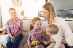 A mulher veio em casa e abraça suas crianças Uma baby-sitter está sentando-se ao lado deles Foto de Stock Royalty Free