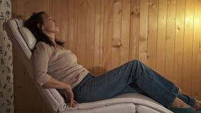 A mulher vem relaxar em casa na poltrona da massagem video estoque