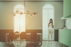 Mulher verde em janelas arqueadas uma sala de jantar Fotografia de Stock