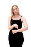 A mulher verific o tempo em seu relógio de pulso Imagem de Stock