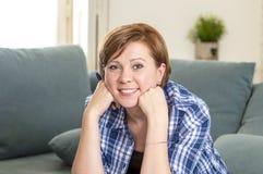 Mulher vermelha atrativa e feliz nova do cabelo ao redor 30 em casa anos de pena de terra arrendada segura de sorriso velha da sa Fotos de Stock Royalty Free