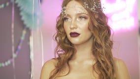 Mulher vermelha bonita atrativa nova do cabelo com giro de levantamento accesory da cabeça da pérola ao redor na frente da câmera video estoque