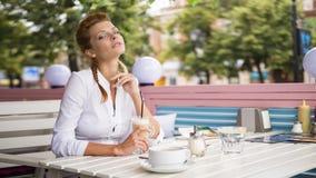 A mulher vermelha bonita sonhadora nova do cabelo senta-se no café do verão, olha-se para fora na rua e bebe-se o latte quente do foto de stock royalty free