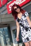 Mulher vermelha do cabelo com o saco de compras contra da entrada da loja Imagem de Stock Royalty Free