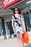 Mulher vermelha do cabelo com o saco de compras contra da entrada da loja Imagens de Stock Royalty Free