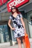 Mulher vermelha do cabelo com o saco de compras contra da loja Imagens de Stock Royalty Free