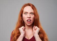 Mulher vermelha do cabelo que faz uma expressão enojado Foto de Stock