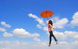 A mulher vermelha do guarda-chuva salta ao céu fotos de stock
