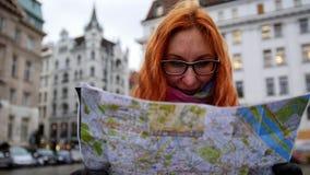 Mulher vermelha nova do cabelo que usa o mapa da cidade no quadrado em Viena, ângulo largo, fim acima Imagem de Stock