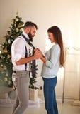 A mulher veste seu laço do noivo na árvore de Natal do fundo Foto de Stock Royalty Free