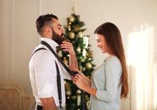 A mulher veste seu laço do noivo na árvore de Natal do fundo Imagens de Stock