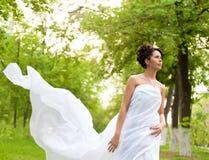 Mulher vestida branca nova que anda no parque da mola Fotos de Stock Royalty Free