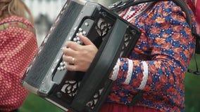 A mulher, vestida em um traje popular, joga o acordeão vídeos de arquivo