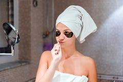Mulher vestida em uma toalha para escovar seus dentes na frente de um espelho no banheiro conceito healty da manh? do bem-estar foto de stock