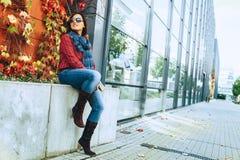 A mulher vestindo da forma senta-se perto do shopping moderno foto de stock royalty free