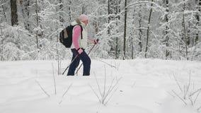 A mulher vestiu-se na roupa morna dos esportes com uma trouxa que anda ativamente em um passeio na floresta que realiza em suas m video estoque