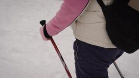 A mulher vestiu-se na roupa morna dos esportes com uma trouxa que anda ativamente no passeio na floresta que realiza em sua mão filme