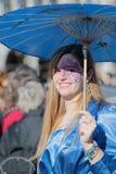 A mulher vestiu-se no azul com um guarda-chuva do parasol durante o carnaval de Veneza Fotografia de Stock Royalty Free