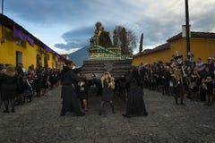 A mulher vestiu-se no preto que leva um flutuador gigante em uma rua da cidade velha de Antígua durante uma procissão da Semana S Imagem de Stock