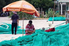 A mulher vietnamiana costura a rede de pesca Imagem de Stock