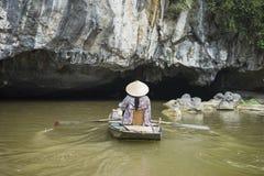 Mulher vietnamiana no barco de fileiras cônico tradicional do chapéu na caverna natural no rio de Ngo Dong, Tam Coc, Ninh Binh, V fotografia de stock