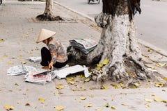 A mulher vietnamiana que veste o chapéu cônico asiático senta e prepara jornais para a venda sob a árvore em Hanoi, Vietname fotos de stock royalty free