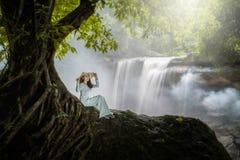 A mulher vietnamiana senta-se abaixo de uma árvore bonita da cachoeira com a Fotos de Stock