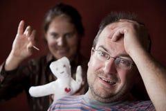 Mulher virada com boneca do vioodoo e o homem culpado Imagens de Stock Royalty Free