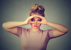 A mulher virada desagradada que olha através dos dedos gosta de binóculos Imagem de Stock Royalty Free
