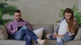 A mulher virada dos jovens é forçada e infeliz quando seu noivo que usa o tablet pc se sentar no sofá em casa imagem de stock royalty free