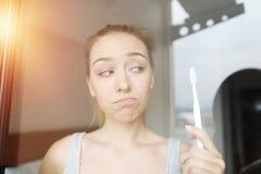 Mulher virada dos jovens com a escova de dentes que olha triste imagens de stock royalty free